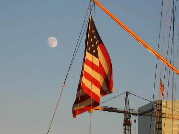 The moon rises behind a large American flag at the stern of the Star of India.