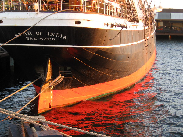 Photo of a magical moment as water glows brightly. Red light reflects from the hull of the Star of India just as the sun is about to set.