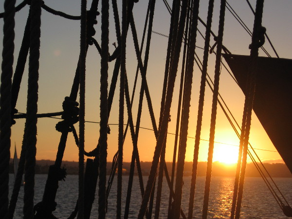 The sun is ready to set behind Point Loma. Photo taken through the rigging of HMS Surprise, one of several amazing tall ships at the Maritime Museum of San Diego.