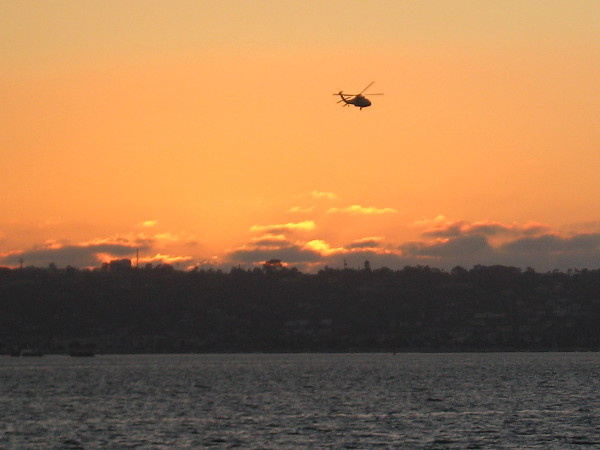 A helicopter flies over San Diego Bay just moments after the sun has set.