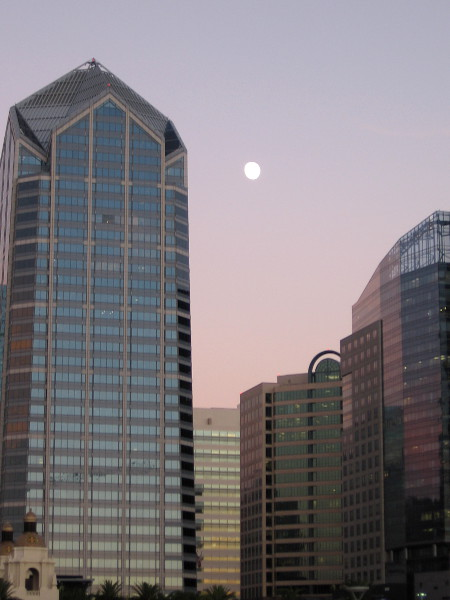 A nearly full moon rises slowly above downtown San Diego a few minutes before darkness falls.