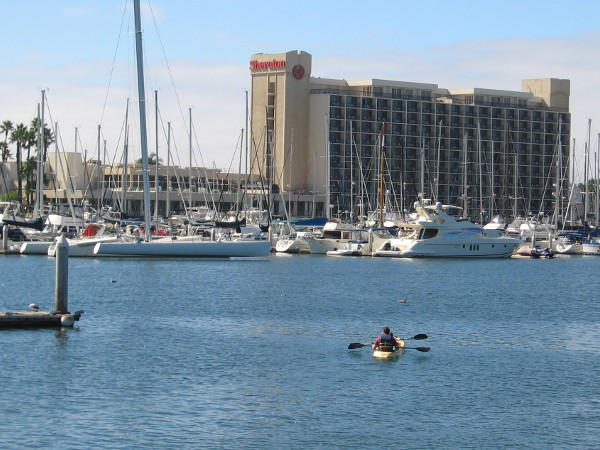 Kayak heads across the water toward boats docked at a Harbor Island marina.