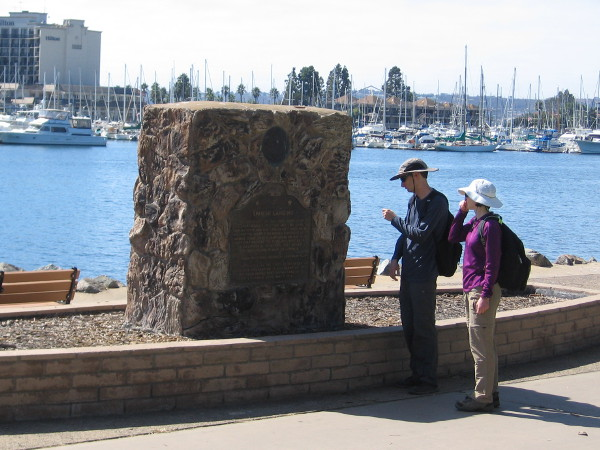 Walkers pause on the path through Spanish Landing to read a California Historical Landmark plaque near the water.