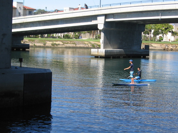 Paddleboarders float down the boat channel between North Harbor Drive Bridge and the adjacent Nimitz Bridge, which is now used by pedestrians. The grass in the distance is part of the Liberty Station Esplanade.