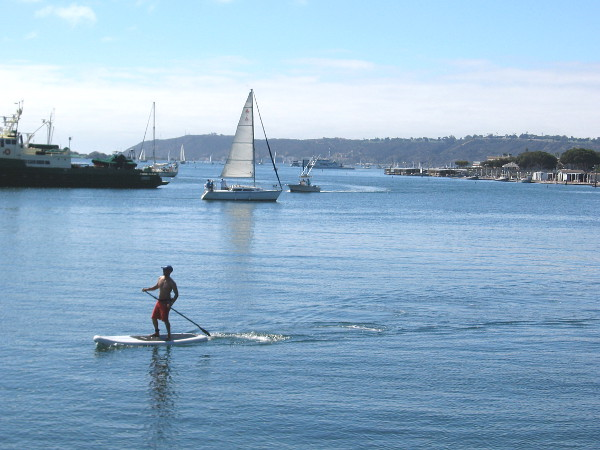 Sailboats, paddleboards and boats of every type out on blue San Diego Bay. The Pacific Ocean lies just beyond the peninsula of Point Loma, in the distance.