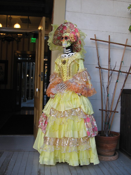 In celebration of Día de los Muertos, or Day of the Dead, two lady skeletons wearing frilly dresses greet visitors to the Cosmopolitan Hotel. Here's one.