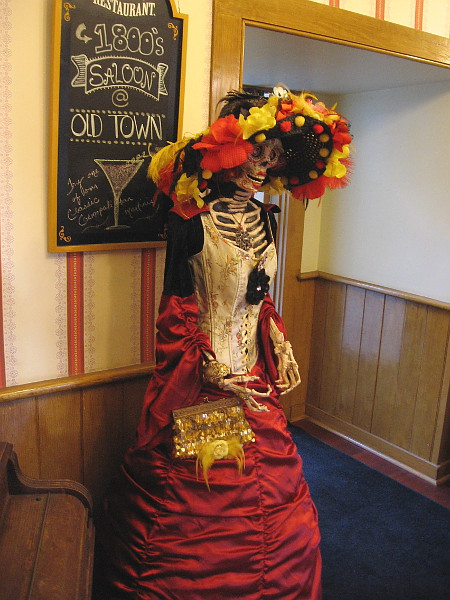 Inside the Cosmopolitan Hotel's saloon, more extremely elegant but skeletal customers are observed.