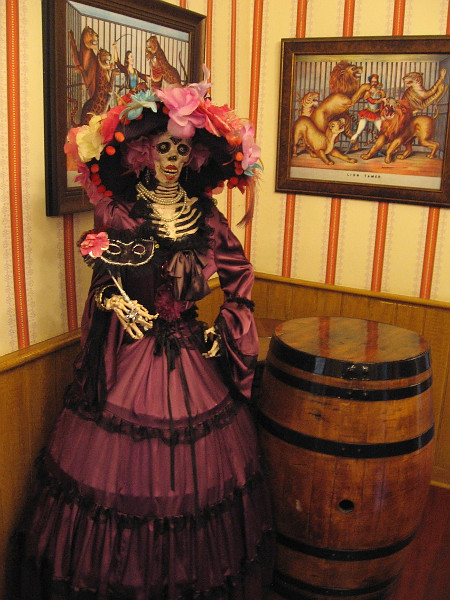 A shy skeleton in quite fancy attire stands silently in the corner of the Old West 1800s saloon.