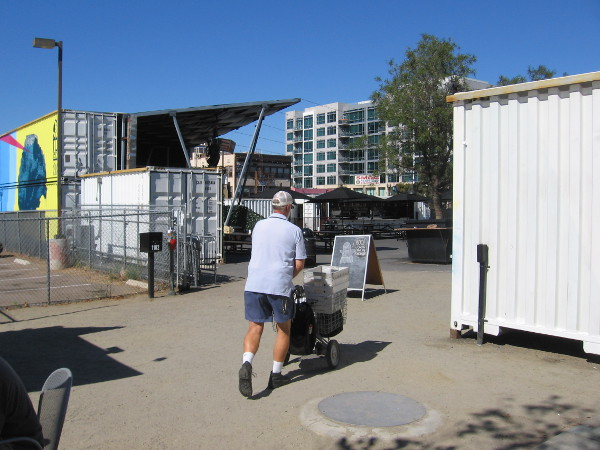 Mail delivery person heads into Quartyard, an unusual community gathering place made from repurposed shipping containers. Coffee, beer, concerts and food trucks are found here.
