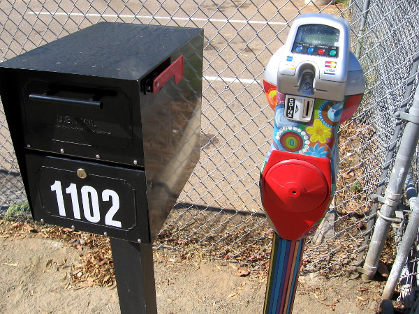 A colorfully painted parking meter stands strangely by the mail box.