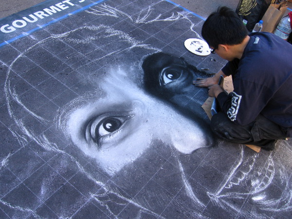 A laughing face slowly takes life. Chalk artists have converged to create beautiful art in Little Italy for Festa!