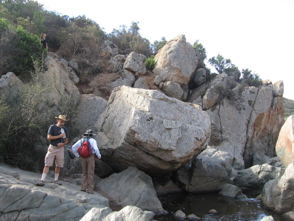 Hikers pause above a pool of water which is captured by large blocks of volcanic rock. When the creek crests, it can rise many feet and submerge this area.