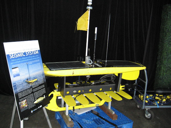 The Autonomously Deployed Deep-Ocean Seismic System's Wave Glider is powered by solar and wave energy. It links with satellites and ocean bottom seismometers to help predict earthquakes and tsunamis.