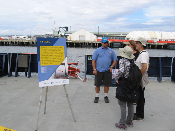 Visitors on the rear deck of RV Sally Ride learn about science on the sea from a crewmember.