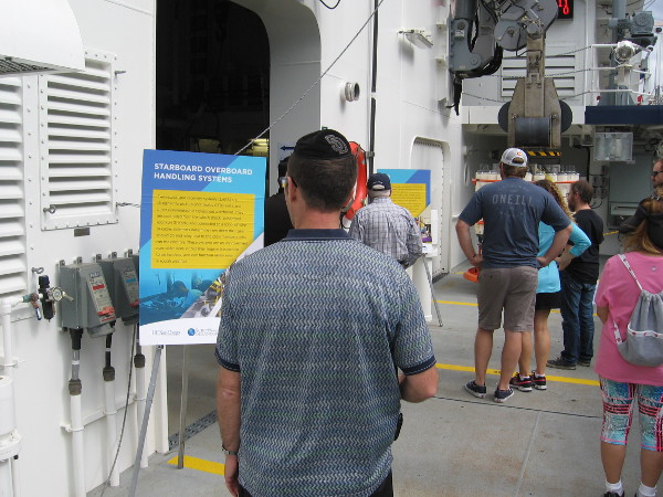 A member of the public reads a sign explaining that the LARS are controlled from the winch shack. Wire or cable is used to lower equipment overboard.