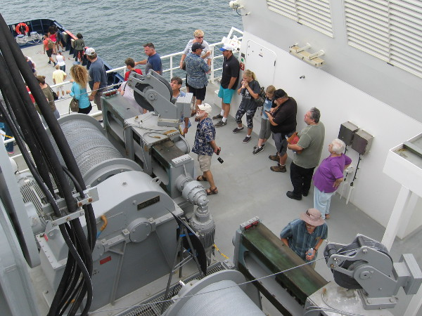 People examine an oceanographic winch. Drums can have upwards of 10,000 meters of wire or cable spooled on them.