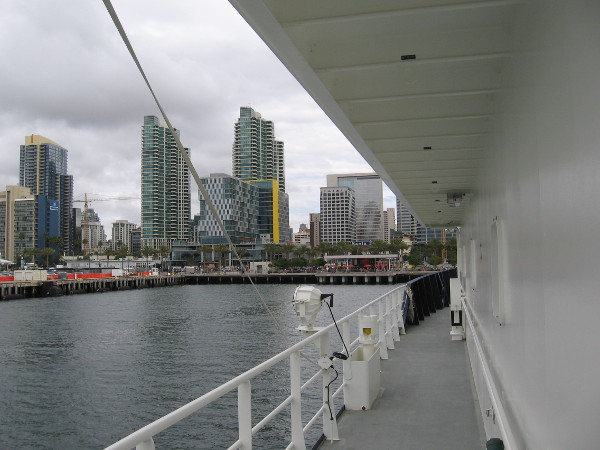 Heading forward along the ship's port side. Downtown San Diego buildings rise across the water.