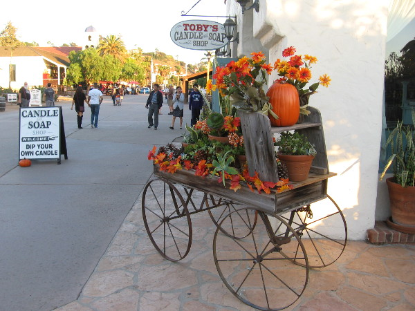 A pumpkin and warm flowers on an antique cart in Old Town San Diego.