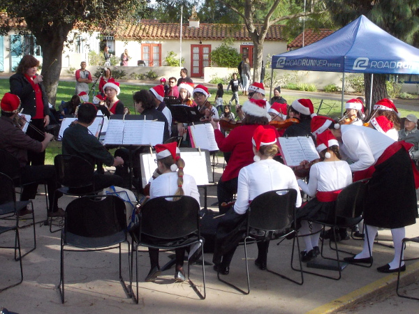 Youthful members of All About Music San Diego prepare to play instrumental music at Christmas on the Prado in Balboa Park.