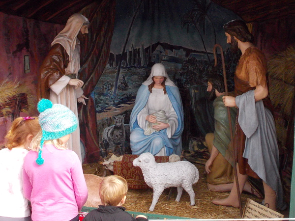 Children view a scene depicting the birth of Jesus in a humble manger.