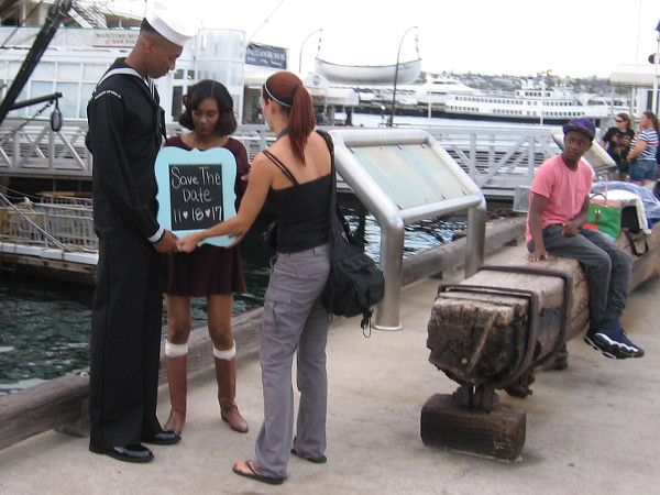 A sailor and a sweetheart have a special date ahead. There is plenty of life on San Diego's Embarcadero late one Saturday afternoon.