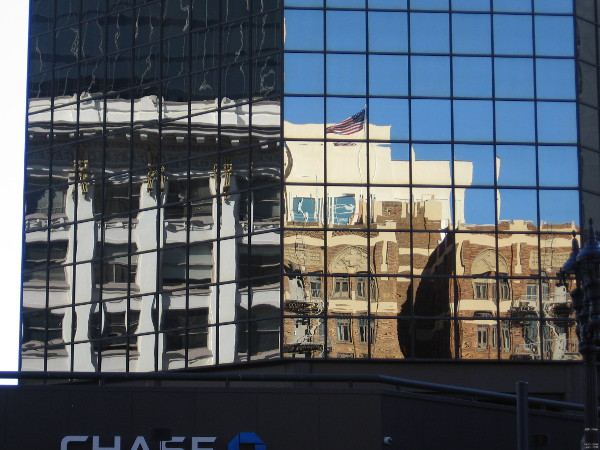 Two buildings reflected in the windows of 101 W. Broadway in downtown San Diego. On the left is the Spreckels Theater Building; on the right is the Sofia Hotel.