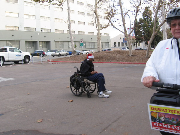 Tourist on a Segway passes a disabled Santa in a wheelchair.