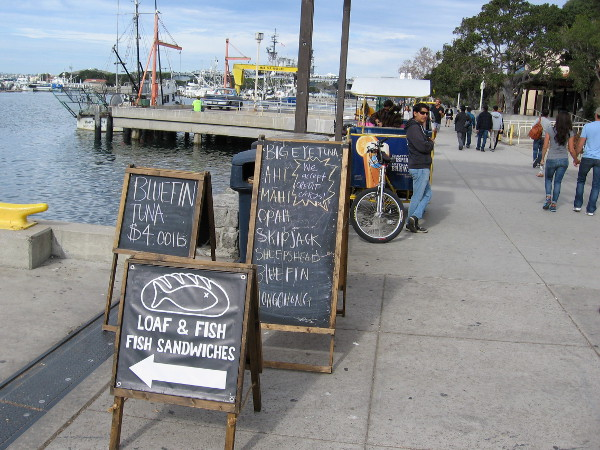 Sidewalk signs try to lure people out onto a pier near Seaport Village. Fresh seafood caught by local fishermen is sold here every Saturday morning.