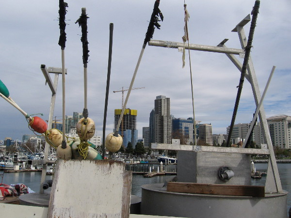 Floats with spear-like poles rise into the sky above downtown San Diego skyscrapers.