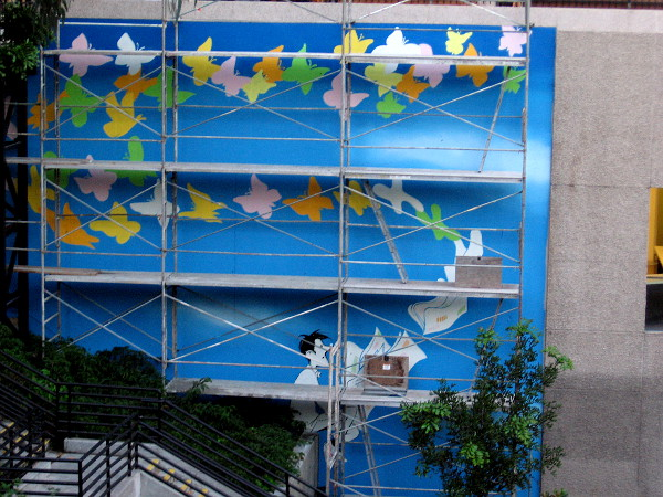 A new mural is being painted on the north side of 600 B Street, the new home of the San Diego Union Tribune. It depicts a man sitting on a wall reading a newspaper. Loose windblown pages transform into colorful butterflies.