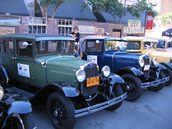 A row of shiny vintage cars on display during the popular downtown San Diego event.