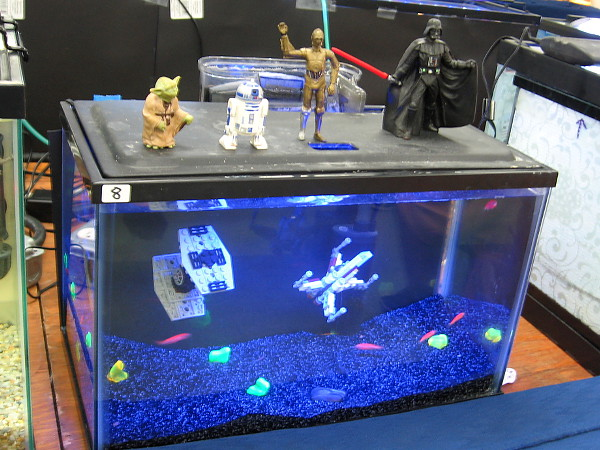 Star Wars characters stand atop an aquarium from a galaxy far, far away. The space-like interior features a duel between a TIE fighter and X-Wing.