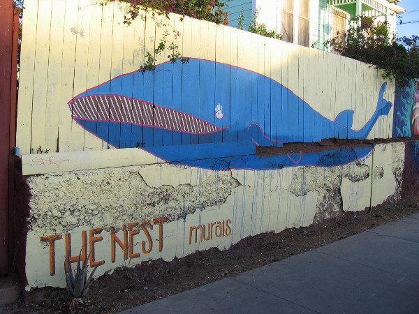 The Nest Murals include a big blue whale on a yellow fence in Barrio Logan, not far from downtown San Diego.