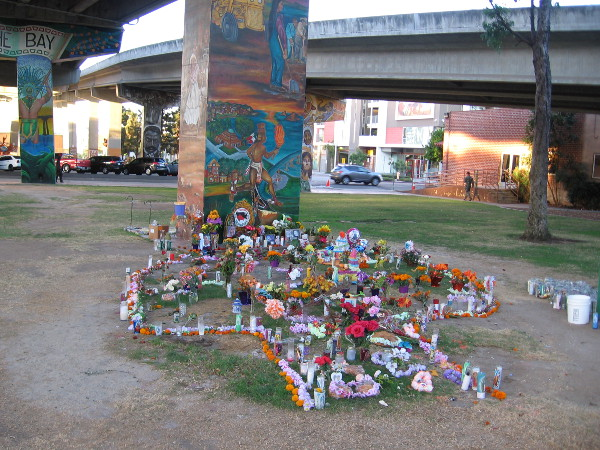 Candles, flowers and other expressions of love stand beside a Chicano Park mural. They memorialize Cruz Elias Contreras, Andre Christopher Banks and Francine Denise Jimenez.