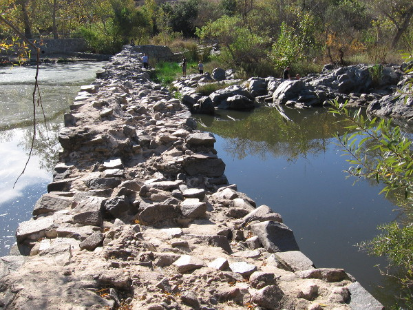 Standing on the north end of the Old Mission Dam. Materials used in constructing the dam include volcanic rock found in this area.