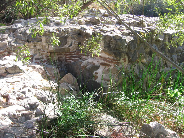 A slot in the dam wall where a water wheel was located. The river water, after driving the wheel, flowed along an aqueduct south to the mission, where it was used to grow crops.