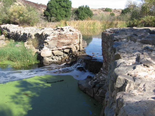 A vertical groove in the dam wall shows where the floodgate used to exist. The dam was completed around 1813, and the long flume to Mission San Diego was completed several years later.