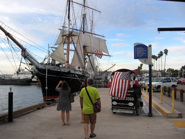 Pedestrians and a flag-draped pedicab approach the famous tall ship Star of India at the Maritime Museum of San Diego.