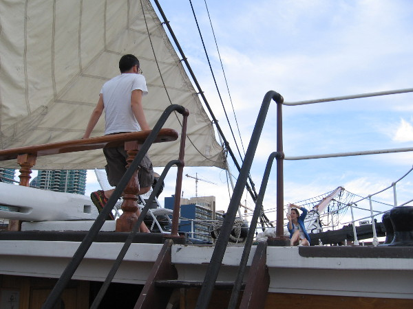 Visitor atop the Star of India's forecastle has his picture taken among sails.