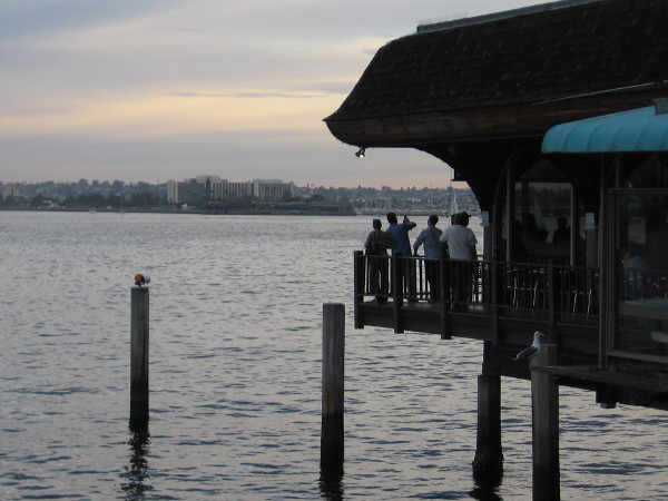 A group watches the sunset above San Diego Bay from the deck of Anthony's Fish Grotto.