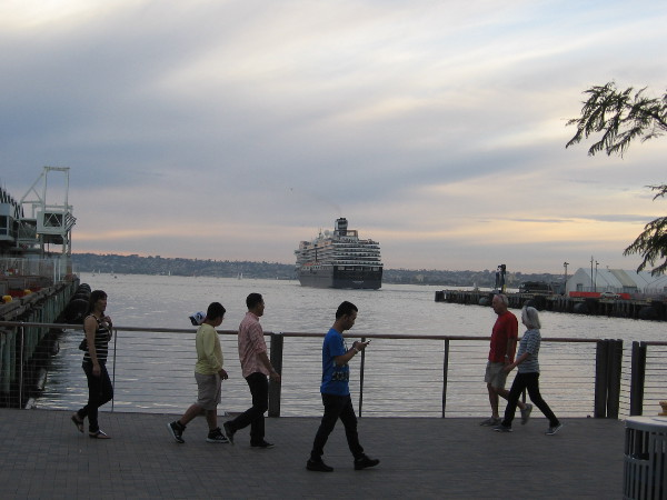 Tourists walk along the picturesque Embarcadero while a cruise ship moves across the bay, making for the Pacific Ocean.
