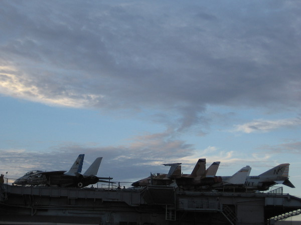 Jet aircraft high up on the flight deck of the USS Midway Museum in the late afternoon.