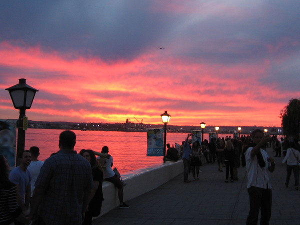A glorious, glowing sunset turns the clouds orange and red. Visitors linger near the water at Seaport Village in San Diego.