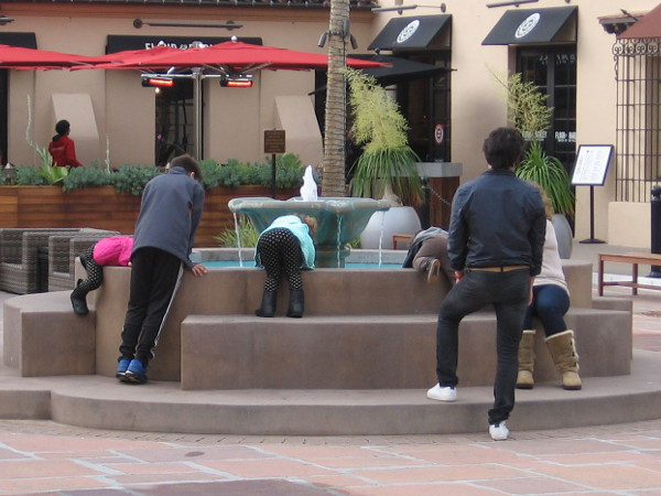 Youth peers into a fountain hopefully. What can one see? Dreams filled with light?