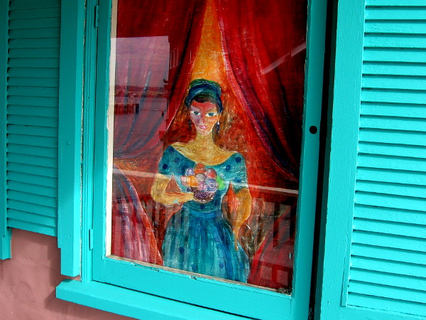 A lady holding a colorful bouquet in the window of Seaport Deli and Salad Bar.