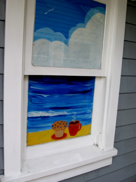 Beach, clouds, muffin and coffee in a window of the Seaport Cookie Company.
