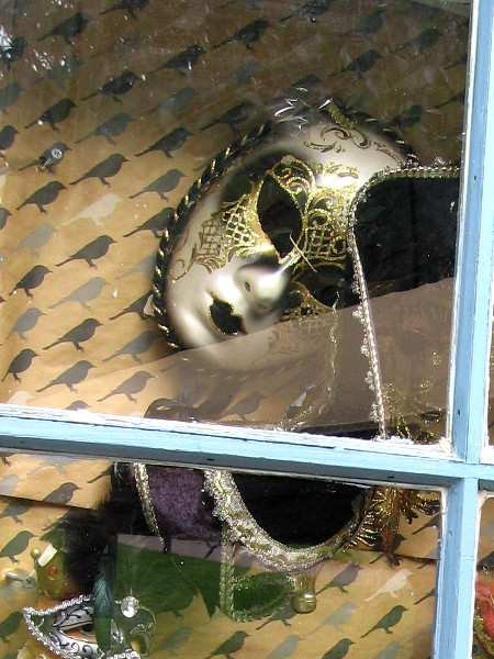 Exotic masks for a masquerade in a window of Upstart Crow Bookstore and Coffeehouse.