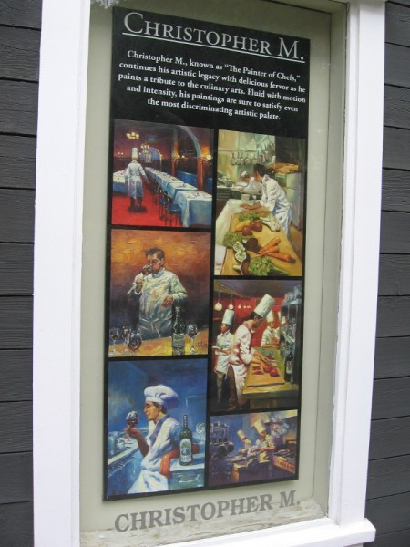 Christopher M., known as The Painter of Chefs, has samples of his work displayed in one window of Exclusive Collections Gallery in Seaport Village.