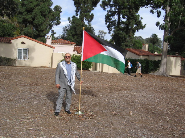 A gentleman from the House of Palestine stands near a flag where a new cottage will be built that showcases Palestinian culture.