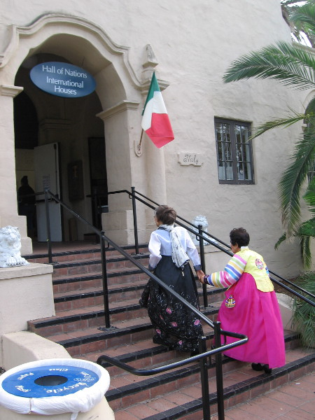 Two ladies in colorful dress enter the Hall of Nations Building for a special groundbreaking reception.